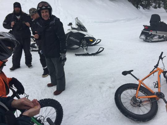 A group of snowmobile riders stop near Brockway Summit at Lake Tahoe to ask questions about fat bike riding on snow.