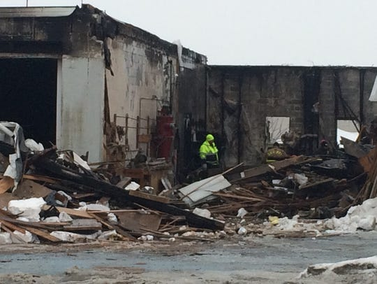 Fire investigators examine the damage after a Tuesday