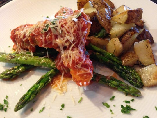 Thin slices of chicken are rolled, then stuffed with gorgonzola, mozzarella and pancetta then served with pomodoro sauce, asparagus and rosemary potatoes.