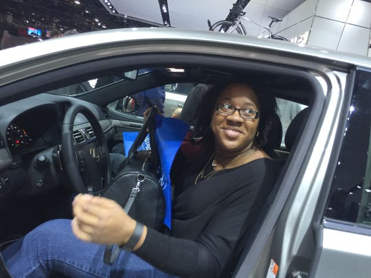 Janell Jackson, 26, of Cincinnati checks out a Lexus at the North American International Auto Show on Saturday, Jan. 16, 2016, at Cobo Center in downtown Detroit.