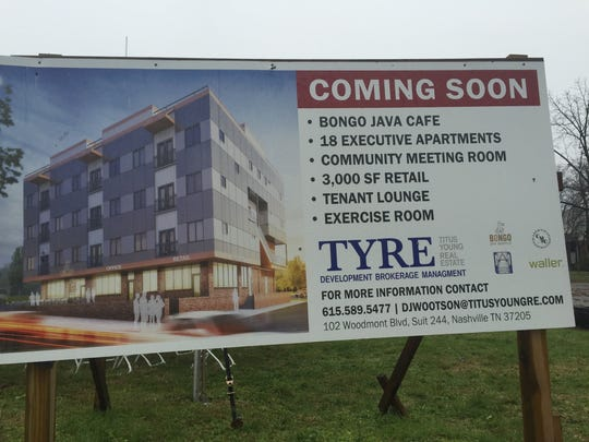 A sign that includes a rendering and information about the 1821 Jefferson mixed-use project.