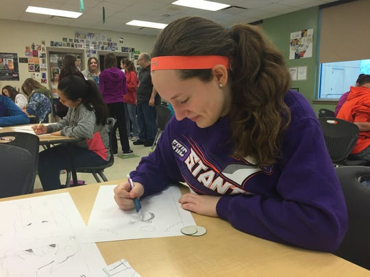 Carlisle Middle School student Payton Baldridge begins work on her final drawing by creating the circles of Captain America's shield.