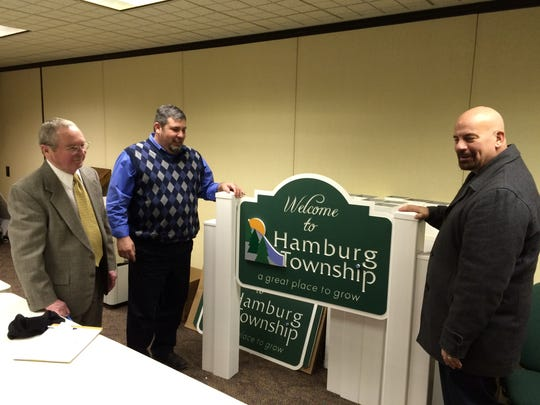 Hamburg Township Clerk Jim Neilson (left), Trustee Mike Dolan (center) and real estate agent Rick Beaudin (right) discuss the importance of identifying Hamburg Township as a community. Six signs welcoming people to the township would be installed after the weather breaks.