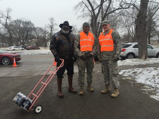 Flint resident John Wiggins, left, pictured with two National Guard members who have been distributing water to Flint residents.