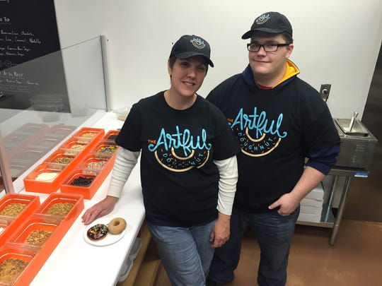 Nancy Broden gets help from her son, Silas Broden, at The Artful Doughnut, where  customized confections are available.