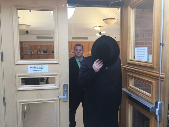 Rabbi Jacob Goldman leaves Ramapo Justice Court  followed by Detective Cyril Kerr of the Rockland District Attorney's Office.