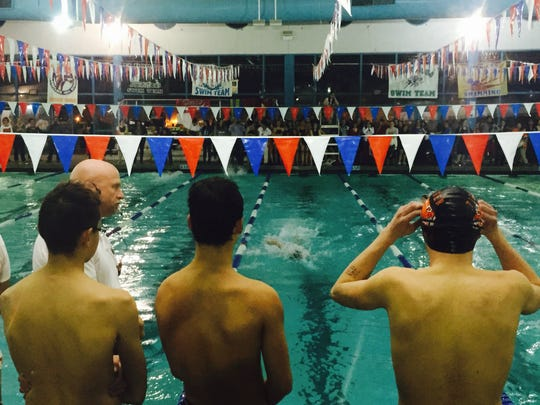 Members of the El Paso High boys 400 freestyle relay team watch as a teammate makes his way down the lane Thursday.