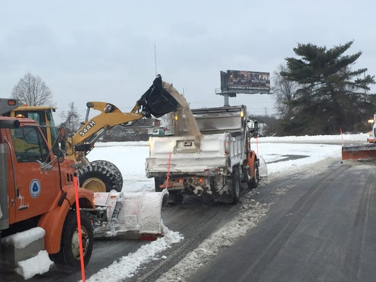 A DelDOT snow plow gets resupplied with salt to sprinkle onto the roadway.