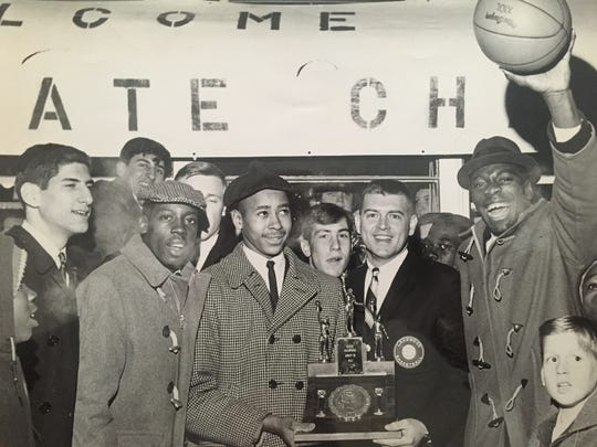 Lakewood's John Richardson (left, holding trophy) stands with teammates, fans and coach Bob Nastase (right, holding trophy) after returning to Lakewood from Atlantic City, where the Piners won the 1967 NJSIAA Group III title.