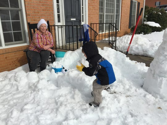 Barbara Rowe watches her grandson Tye scoop up a handful of snow for a snowman he built with his grandfather, Jack Rowe.