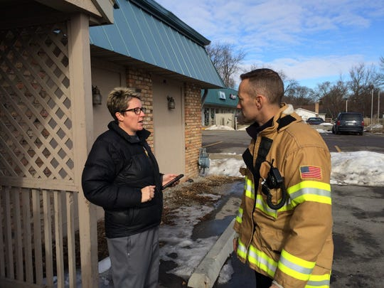 Susie Spalj, left, the owner of Shakespeare's Pub and Grill, speaks to Iowa City Fire Department Battalion Chief Brian Platz after crews extinguished a fire Thursday morning.