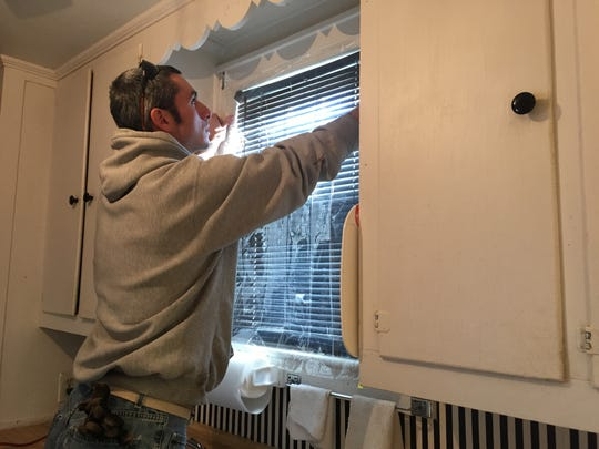 Volunteer Bob Mele places a sheet over a kitchen window