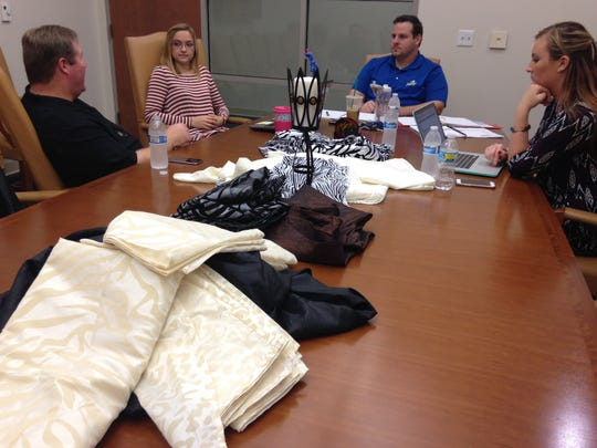 Faculty adviser Scott Lee, left,  meets with Paige Martin, Todd Reed and Sabrina Bracken, the student group planning Wanderlust 2016. Table linen samples for being considered for the event are in the foreground.