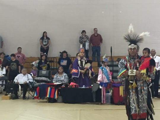 A dancer carries Nicholas into his first pow-wow circle,