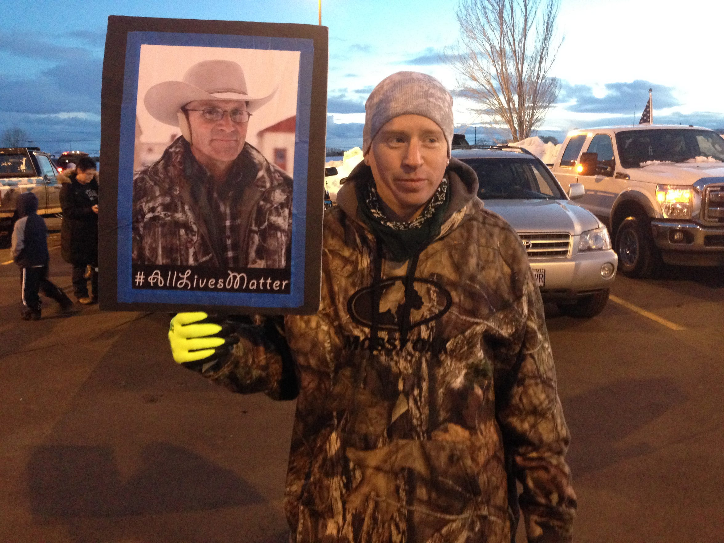 Tony Atencio of Burns, Oregon, holds a photo of rancher Robert ``LaVoy'' Finicum at a rally against Finnicum's slaying by law enforcement officers, and the presence of numerous heavily armed law enforcement officers at the standoff, Saturday, Jan. 30, 2016, in Burns, Oregon. Four people occupying the wildlife refuge held their position Sunday. They have demanded that they be allowed to leave without being arrested.