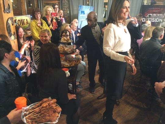 "Al Roker, standing behind Savannah Guthrie, samples some State Fair-style fried goodies during the filming for the ""Today"" show at West End Architectural Salvage."