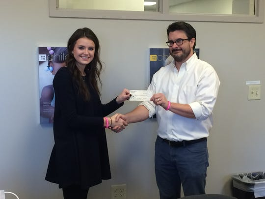 Gracie organized a benefit concert to help support a bully prevention program at Cincinnati Children's Hospital Medical Center.  She raised $3,100 and presents Dr. Ryan Adams a check.