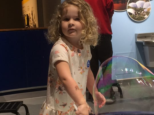 Ammi Allen, 3 1/2, of Burlington, plays with bubbles at the Montshire Museum of Science.