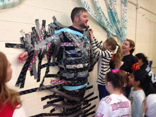 "Jennie E. Smith Elementary School students duct tape their assistant principal, John Lynch, to the wall for a ""Stick it to Cancer"" fundraiser."