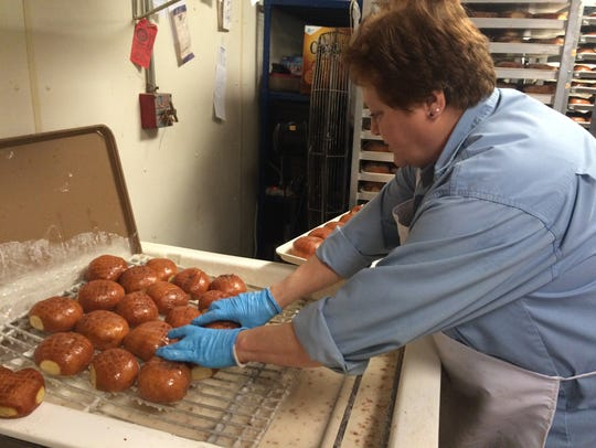 Debbie Curran, co-owner of Looney Bakery, glazes dozens