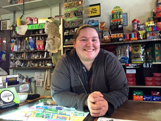 Misty Sherman stands at the checkout counter -- surrounded by the faces of townsfolk in their contributed photos -- at Katy-Did's grocery store in downtown Bussey.