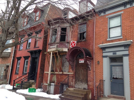 The building at 353 S. George St. in York is seen here with a beam supporting a bay window. The blighted home is slated for renovation by a York developer who is planning an urban infill development project on the block.