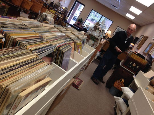 Bill Hetherington searches Tuesday for the jacket of a John Lennon record at his newly opened antique store in Salisbury.