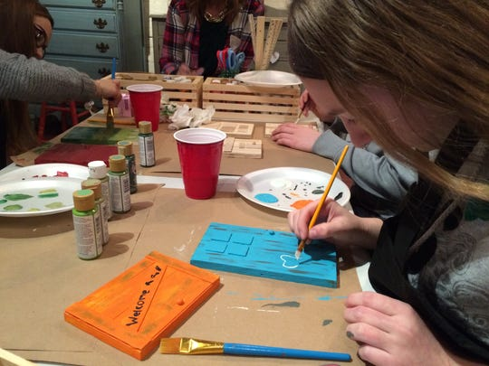 Peyton Bennett, a girl scout from Pinckney, paints a tooth on a fairy door she is making for a dentist's office.