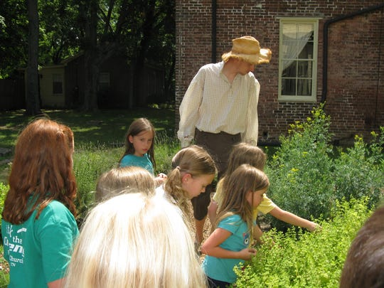 Connor Moss leads campers on an exploration of the herb garden at Oaklands Mansion.