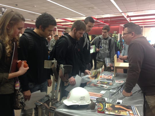 Port Huron High School students listen to Dan Ferqueron, a representative for Michigan Regional Council of Carpenters, at a college fair at the school's media center on Thursday.