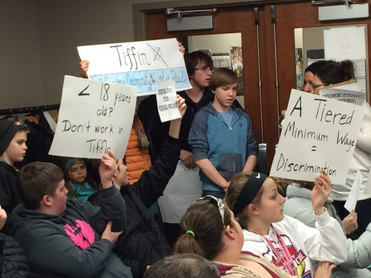 Teenagers hold signs at a Tiffin City Council meeting Tuesday night protesting an ordinance that would pay workers under 18 a lower minimum wage than adults.