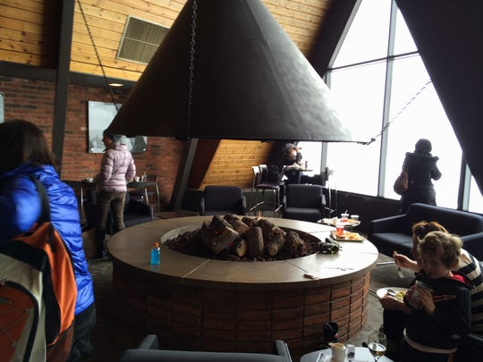 A large round gas fire pit warms skiers and snowboarders in Mount Brighton's Ore Creek Mountain Grill, Friday, Feb. 12, 2016