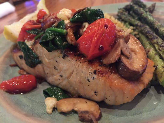 Sautéed spinach, mushrooms, red and yellow cherry tomatoes and wee blue cheese nuggets crown salmon at Kona Jack's.