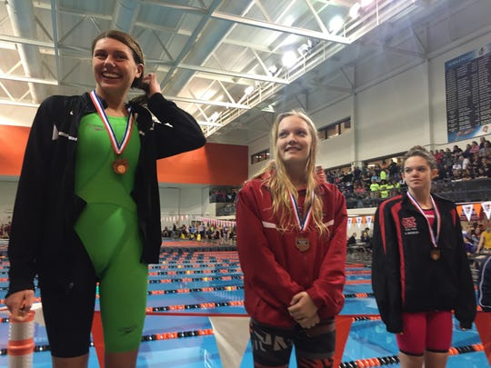 Colonel Crawford's Chloe Grove beams from the awards podium after finishing fourth in the 200-yard freestyle at the Division II district swim meet at Bowling Green. Mansfield Christian's Abby Reynolds (far right) was sixth.