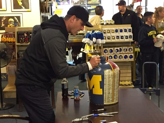 Jim Harbaugh autographs a Little Brown Jug at the M Den in Ann Arbor on Friday, February 19, 2016.