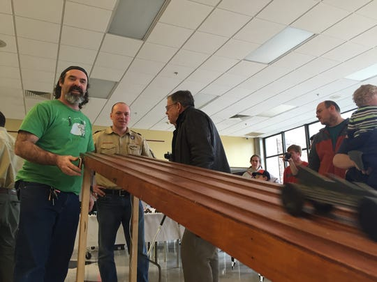 PINEWOOD DERBY: Chuck McKenna, who lost in the first-ever Daddy Derby, races his car against his son's at the Cub Scout's annual Pinewood Derby on Saturday.