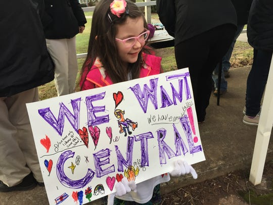 Naomi Pratt holds a sign outside Central Elementary School during a march in January. School board members voted earlier this month to close the school.