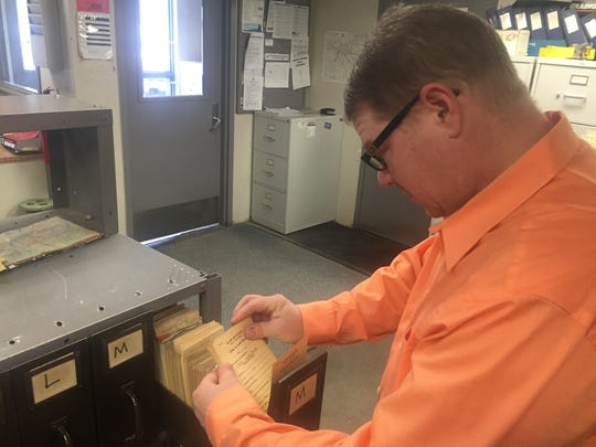 Southfield Public Works Manager Larry Sirls flips through old file cards listing details on the city's 20,400 water service connections.