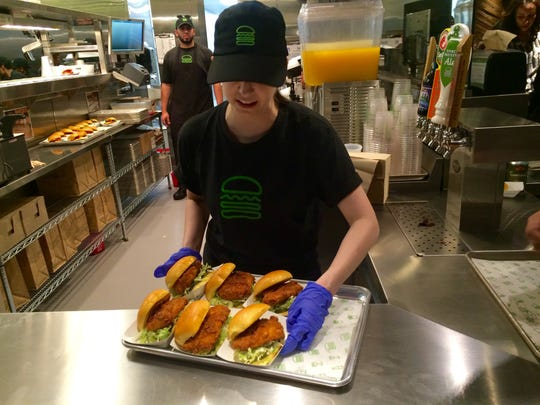 A Shake Shack employee gets ready to serve a tray of
