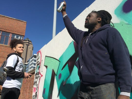 A local street-artist who goes by Asphate teaches Des Moines students how to paint a graffiti in the Des Moines Social Club courtyard.