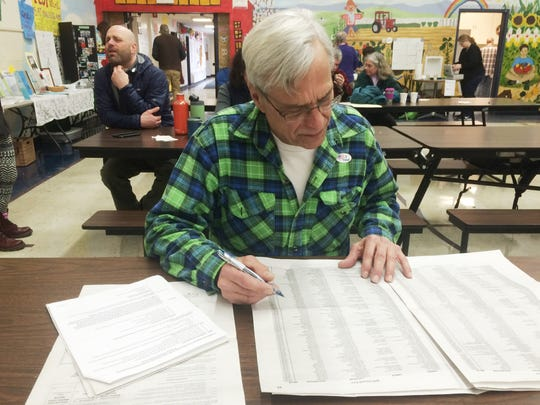 Huntington Selectboard member Roman Livak looks over the local school budget Tuesday during Town Meeting Day.