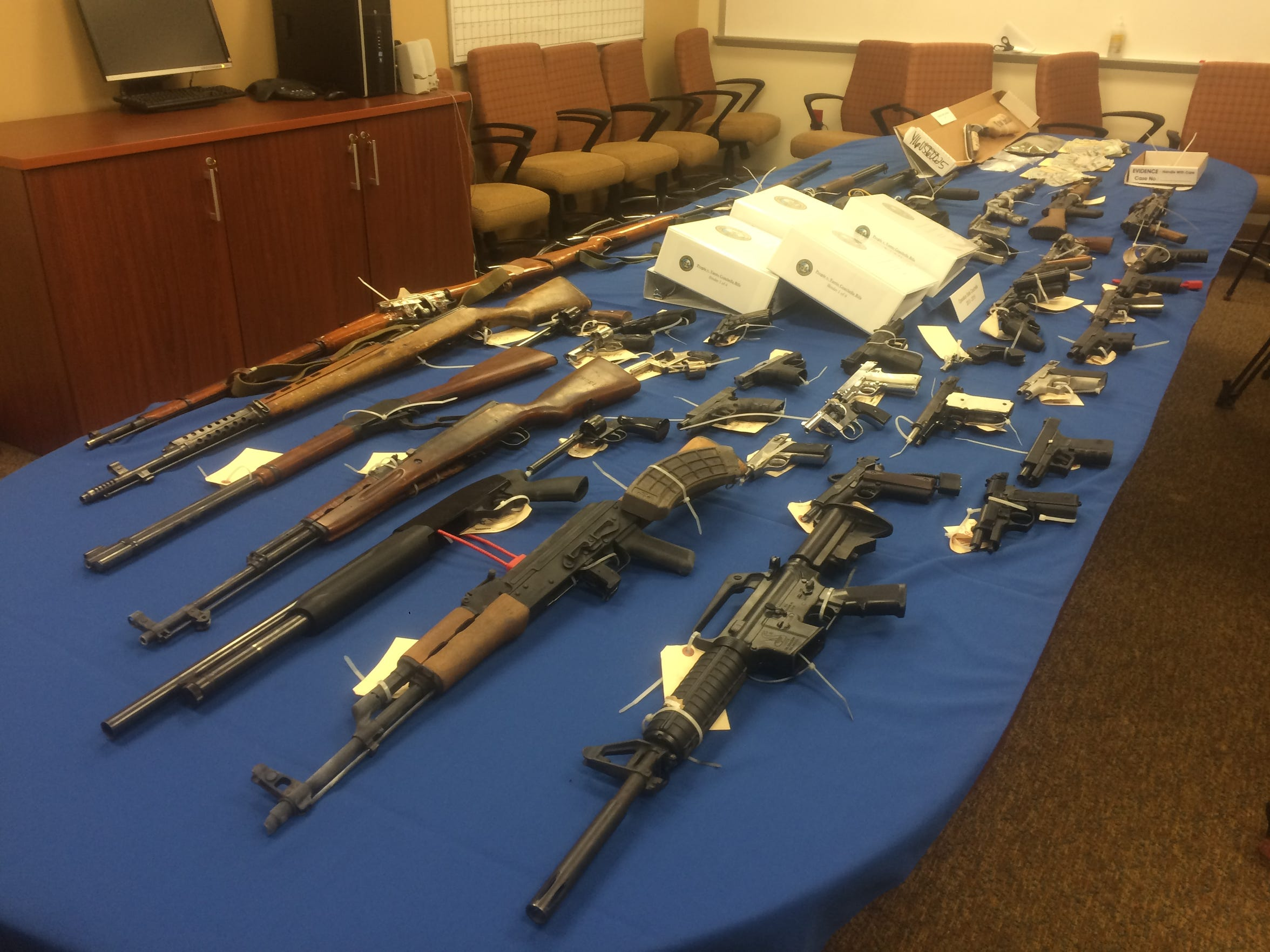 Law enforcement personnel at the sheriff's station in Thermal display a collection of guns seized from Varrio Coachella Rifa during raids.