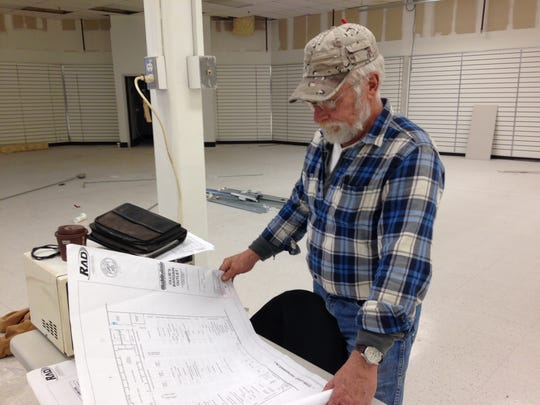 Mitchell Wells, owner of Quality Framing in Medina, studies blueprints at 861 North Parkway.