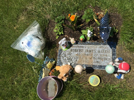 Mementos are left at the grave last summer of Angela Alexie's son, who would have named her baby Robert.