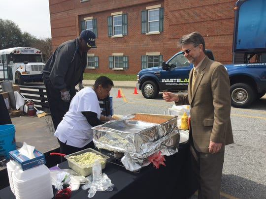 """A customer gets a free plate of fried fish, baked beans and cole slaw from a Soapstone Baptist Church volunteer at the Pickens Innovation Center Commercialization Day """"Launch"""" on Monday."""