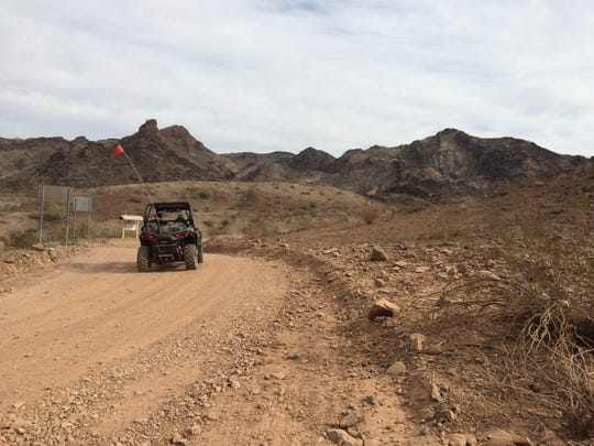 An ultra-terrain vehicle embarks on the rough five-mile unpaved road to the Desert Bar outside Parker.