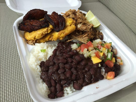 The Lechón Asado Plate at Havana Cabana is served with maduros, tostones, black beans and rice.