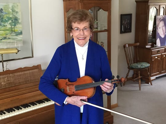 Elva Newdome poses at home with her violin.