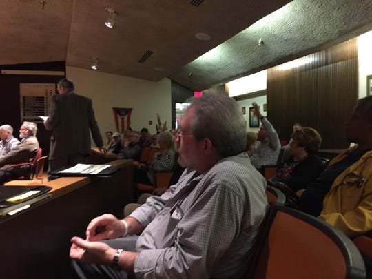 Woodland residents who oppose construction of a three-story housing complex raise their hands to show their opposition.