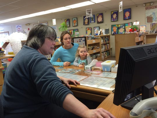 Beth Lokken, Youth Services Librarian with the Sturgeon Bay Branch of the Door County Library shows Rachel Maurer and her daughter Sonora around the new Community Resources page created by the Door County Partnership for Children and Families.